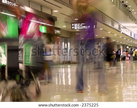 Motion blur image of people carrying luggage in a Japanese Airport.