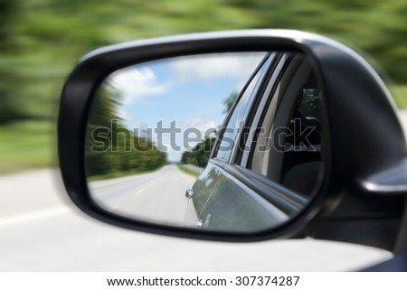 Photo of motion blur image of street from the sideview mirror
