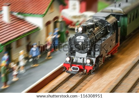 motion blur of a model railroad steam locomotive (with fake number) speeding through a station
