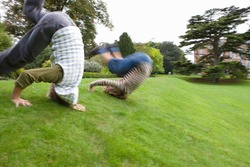 Motion blur of a young boy and a girl rolling down a hill slope.