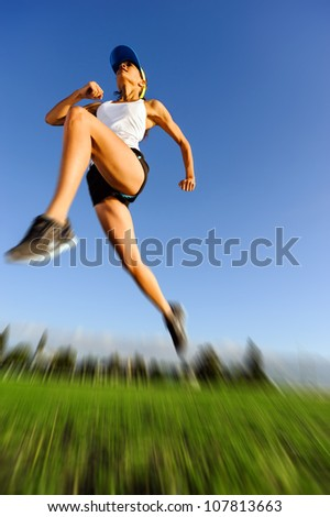 motion blur of athlete jumping outdoors with blue sky and green grass