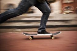 Motion blur of fast skateboarder feet moving