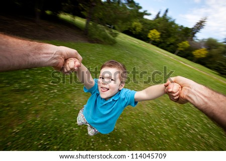Motion blur of father holding onto son's arm while spinning. Sharp focus on eyes