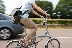 Motion blur of mid-section of a young woman with a sling bag on a bicycle riding on a street.
