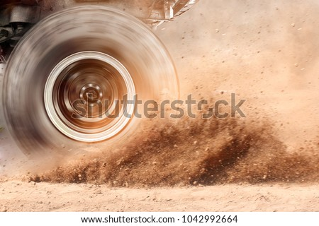 Motion blur of the wheels tires and off-road that goes in the dust of the desert through the wheels on the sand #1042992664