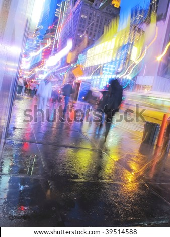 Motion blur ? people walking at Times Square, New York, at night in rainy weather