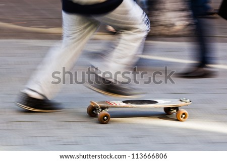 motion blur picture of an unrecognizable boy running with his skateboard
