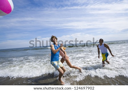 Motion blur shot of a group of friends playing with ball in water