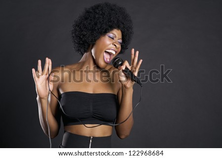 Motion blur shot of a woman singing on microphone over colored background