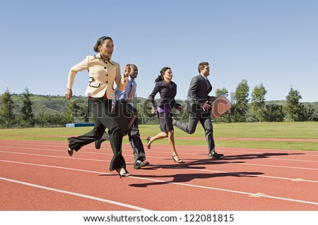 Motion blur shot of four business people running together on racing track