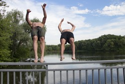 Motion blur Two guys are jumping off the bridge into the river Friends jumping together in the water Summer swimming Vacations teens. holidays
