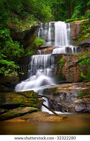 Motion Blur Waterfalls Nature Landscape in Blue Ridge Mountains with green trees, orange rocks and flowing water