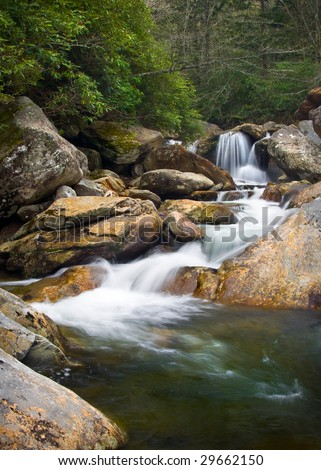 Motion Blur Waterfalls Nature Landscape in Blue Ridge Mountains with green trees, rusty natural orange rocks and flowing water