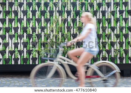 Motion blure of woman riding bycicle by green urban vertical garden wall in Ljubljana, European green capital of Europe 2016. Sustainable green city concept. ストックフォト ©