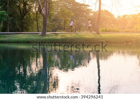 Motion blured of people are running and cycling in urban park with water reflection.