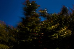 Motion-blurred, abstract, colorful, bushy trees with bright light-streaks and dark shadows on vibrant, deep blue sky