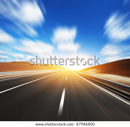 Motion blurred asphalt road and cloudy blue sky - stock photo