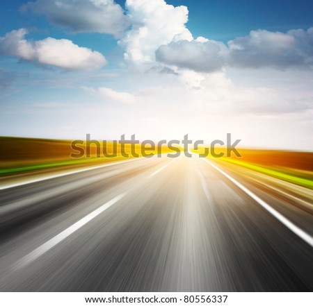 Motion blurred asphalt road and sky with clouds