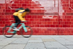 Motion blurred bike. Young afro man and his fixed bike in a suburb of London