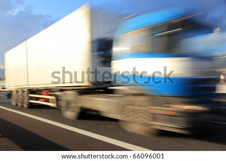 Motion blurred blue truck on highway