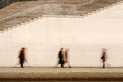 Motion blurred business people walking in front of a bright concrete wall.