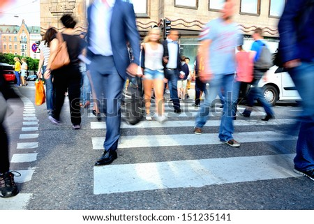 Motion blurred crowd crossing street - stock photo