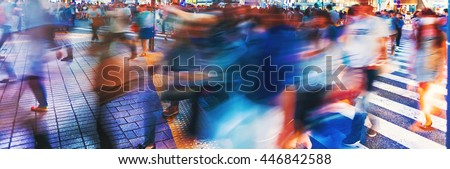Motion blurred crowds converge at Shibuya Crossing, one of the busiest crosswalks in the world. Tokyo, Japan