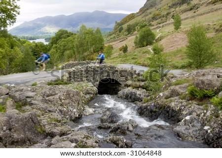 Motion Blurred Cyclists Crossing Ashness Bridge, Lake District England