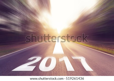 Motion blurred empty asphalt road and New year 2017 concept. #519261436
