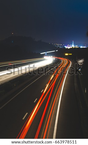 Motion blurred light tracks glowing to the darkness of highway traffic. Long time exposure photography.
