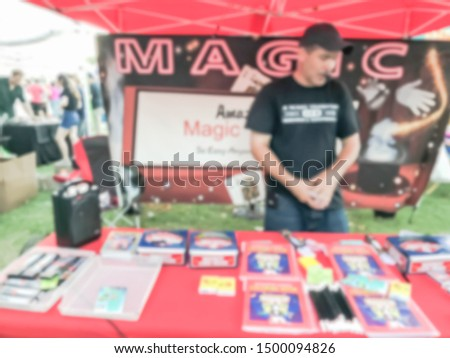 Motion blurred magician with mouth speaker showing magic tricks at his booth of local event festival near Dallas, Texas, USA. #1500094826
