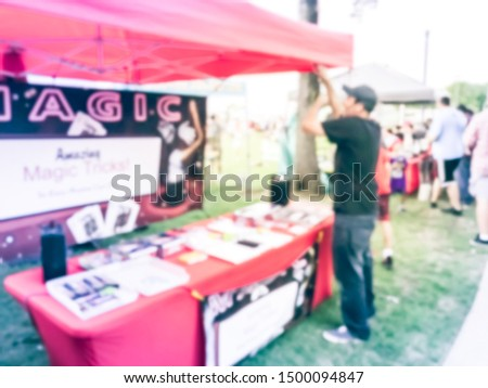 Motion blurred magician with mouth speaker showing magic tricks at his booth of local event festival near Dallas, Texas, USA. #1500094847