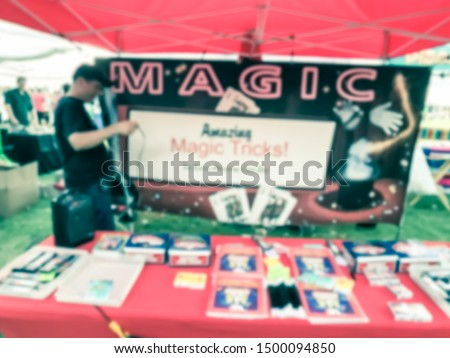 Motion blurred magician with mouth speaker showing magic tricks at his booth of local event festival near Dallas, Texas, USA. #1500094850