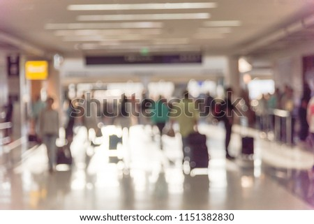Motion blurred motion people walking with luggage at American airport. Abstract blurry passengers or tourist with bag, back view. Defocused traveler away at hallway terminal, morning lights backlit #1151382830