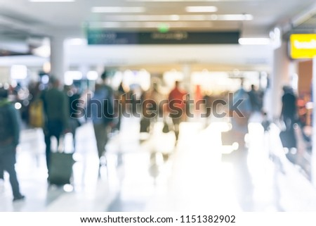 Motion blurred motion people walking with luggage at American airport. Abstract blurry passengers or tourist with bag, back view. Defocused traveler away at hallway terminal, morning lights backlit #1151382902