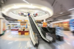 Motion blurred people, store and escalator in shopping mall.