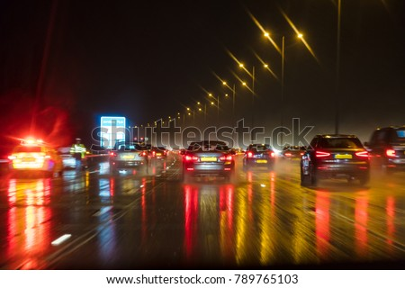 Motion blurred photograph of traffic at in night in the rain on a British motorway with police officer and car