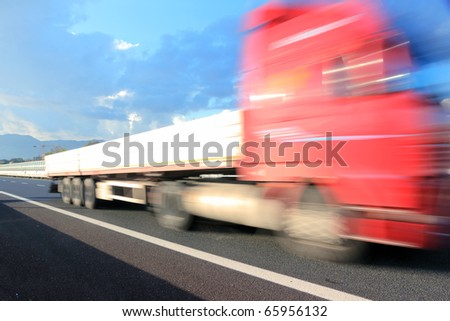 Motion blurred red truck on highway - stock photo
