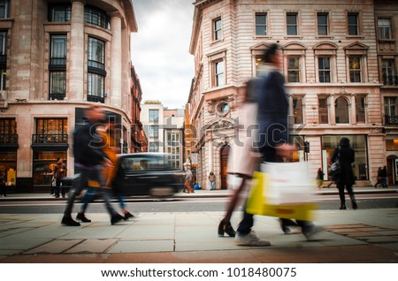 Motion blurred shoppers carrying shopping bags on Regent Street, London.