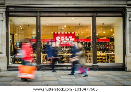Motion blurred shoppers walking past  window display