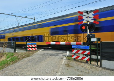 Motion blurred train passing a railroad crossing. Dutch signs warning not to cross and red lights flashing.