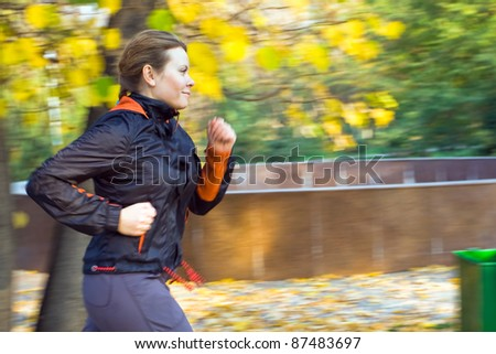 Motion blurred young attractive woman running in forest