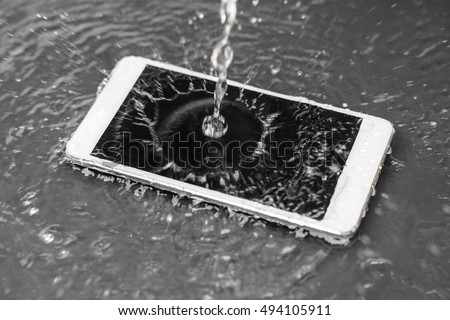Shutterstock Motion movement of water poured over a smartphone / a wet smartphone concept