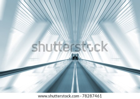 motion of escalator in symmetrical glass corridor