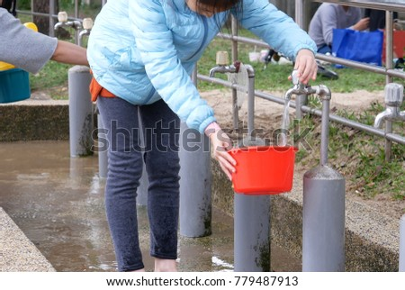 Motion of woman receiving water into a pot for washing hand at park