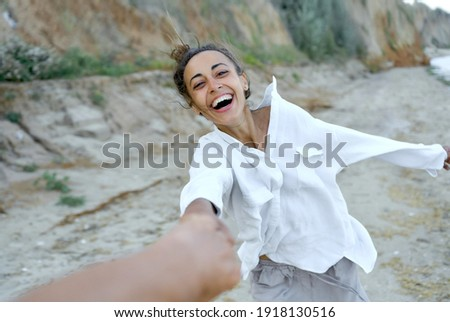 Motion portrait laughing woman holding hand boyfriend and whirling by wild beach, expressive emotions. Real life authentic people Stock photo ©