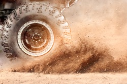 Motion the wheels tires and off-road that goes in the dust of the desert through the wheels on the sand