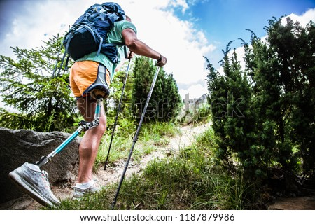 Motivated active male tourist with prosthesis going up while trying Nordic walking