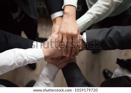 Motivated business people put hands together, sales team engaging in teambuilding activity promising help in collaboration, commitment in teamwork, unity trust and support concept, close up top view
