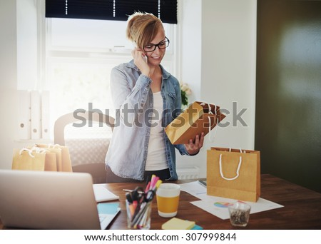 Motivated businesswoman placing orders on the phone for the packaging for her new online web based store as she holds a brown paper gift bag in her hand